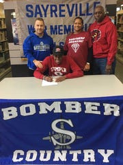 Sayreville's Elijah Clark, flanked by Bombers' head football coach Chris Beagan and Clark's parents, Marcia and Anthony, signed a National Letter of Intent with Temple University on Wednesday.