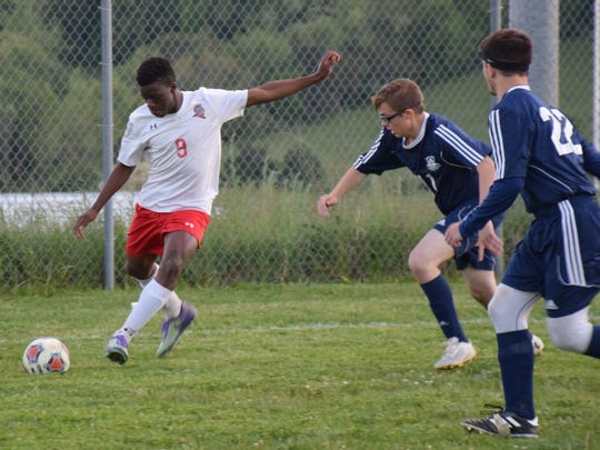 Riverheads' Josh Akinwumi  sends the ball toward the goal as Page County's Anthony Olsen, center, and Nathan Myers move toward him during the first half of their Shenandoah District boys soccer game on Monday, May 8, 2017, at Riverheads High School. The Gladiators won 2-0.