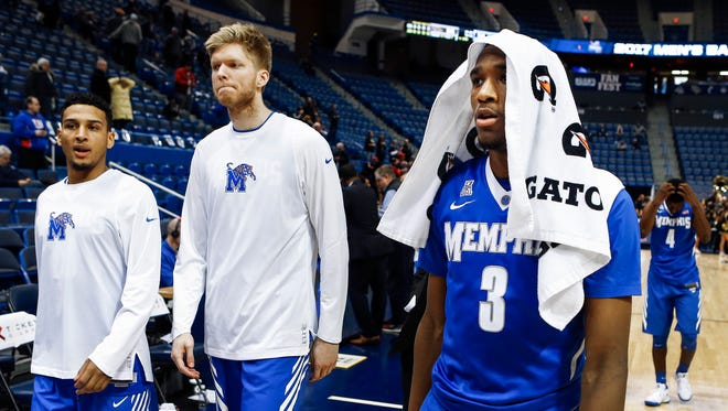 Memphis teammates Christian Kessee (from left), Chad Rykhoek and Jeremiah Martin walk off the court after falling to Central Florida 84-54 in their second-round match up at the American Athletic Conference tournament in Hartford, Conn.