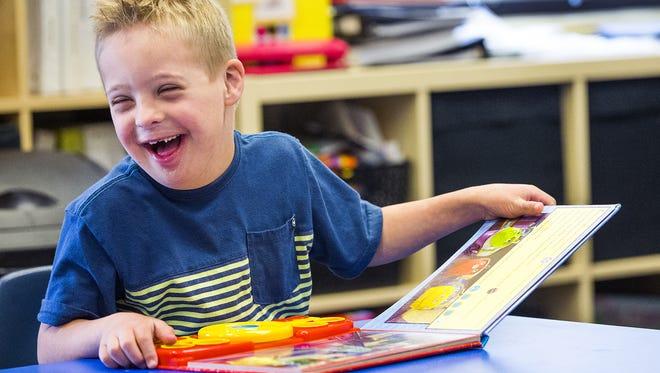 Zachary Branton, 6, enjoys his book in the kindergarten class at Lauren's Institute For Education in Gilbert.