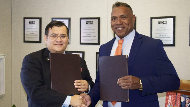 Hector Huerta Nava (left), deputy consul of Mexico, and Coachella Valley Unified School District Superintendent Darryl Adams shake hands after signing a memorandum of understanding to aid Spanish-speaking adults in completing their education.
