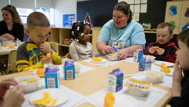 Teacher Patty Cronin helps three-year-old Makayla Grant open her package of cereal during preschool in Philadelphia, Friday, Jan. 6, 2017. Thousands of Philadelphia toddlers are starting 2017 in a city pre-kindergarten program, launched this week alongside a new sugary beverage tax created to fund it.