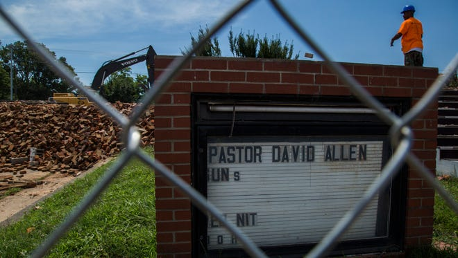 A construction worker and piled bricks stand behind the remaining sign for Pastor David Allen at Mount Olive Baptist Church.