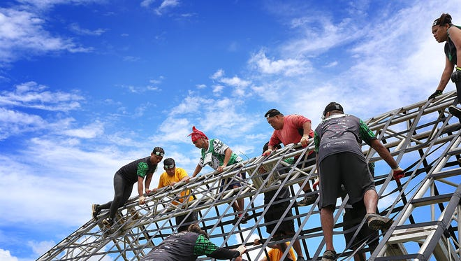 Special Olympic athletes maneuver over the 22-foot cargo net A-frame toward the end of the 2017 Trench Challenge five kilometer course.