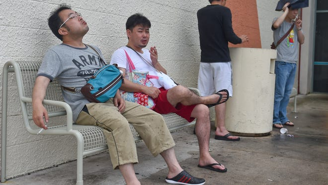 In this file photo, hoppers take a smoke break in a designated smoking area outside Guam Premier Outlets in Tamuning.