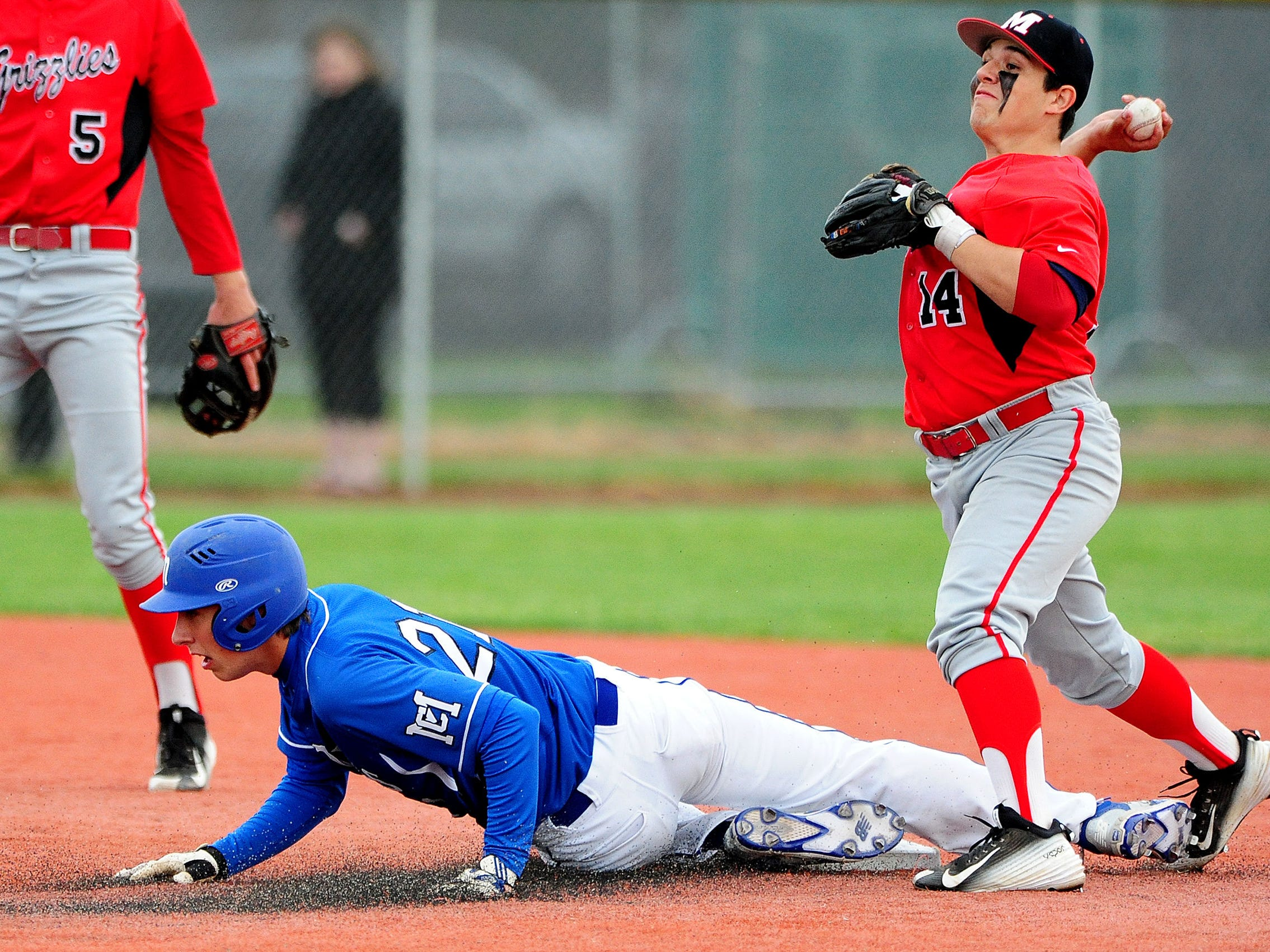 McNary's Matthew Ismay slides into second base as McMinnville's Kyle Casey throws to first base for a double play, on Wednesday, May 13, 2015, in McMinnville.