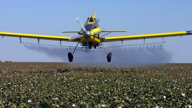 In this 2001 file photo, a crop dusting plane from Blair Air Service dusts cotton crops in Lemoore.