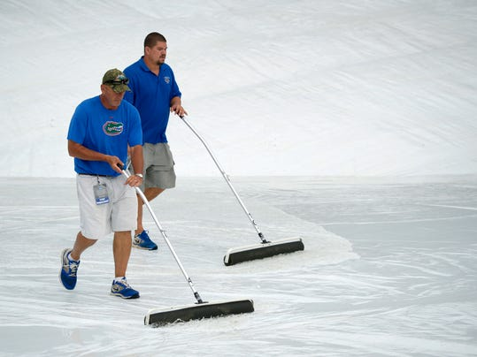 Members of the grounds crew use squeegees to remove water off the infield tarp during a rain delay in the fourth inning of an NCAA college baseball regional tournament game between Long Beach State and North Carolina in Gainesville, Fla., Sunday, June 1, 2014. (AP Photo/Phelan M. Ebenhack)