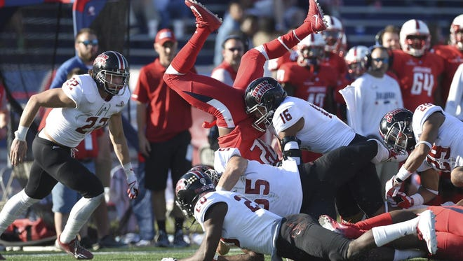UL's Denarius Howard (16) finishes off a tackle and Tanner Wiggins (22) closes in as South Alabama's Tra Minter goes airborne on a second-quarter kickoff return in the Ragin' Cajuns 19-14 win at South Alabama.