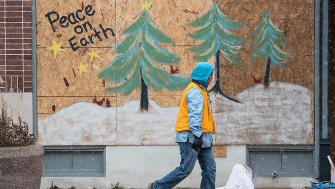 A woman passes a painting on plywood near Ferguson City Hall.