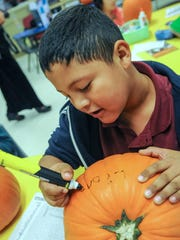 Lionel Cervantes, 8, puts his name on his pumpkin after receiving it from Crop Production Services on Friday at Vado Elementary School.