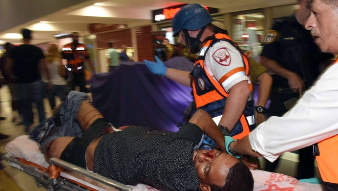 A wounded Eritrean man who later died of his wounds, is evacuated at the main bus station in the southern Israeli city of Beersheva on October 18, 2015, after he was mistakenly shot by an Israeli security guard and beaten by a mob during an attack in the Israeli city of Beersheba following a deadly assault by a gunman at the station.