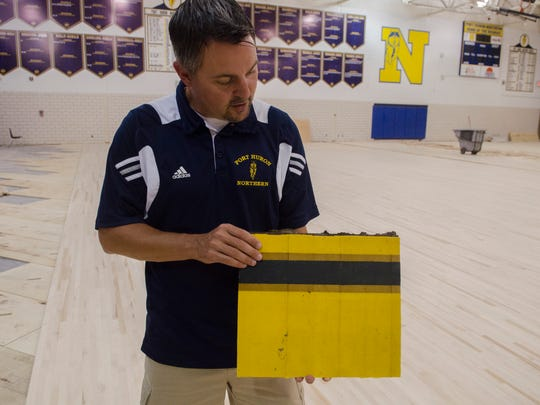 "Port Huron Northern Athletic Director Jason Kasparian shows compares the original floor piece he is holding to the new flooring Friday, July 6 of the Port Huron Northern gym. The floor is being replaced through the ""Fund Our Floor"" campaign."