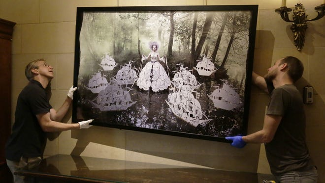 """Aaron Sherer, executive director of the Paine Art Center and Gardens in Oshkosh, along with Keith Nelson of 7th Floor Studios in Milwaukee, hang """"The Queens Armada"""" in the foyer of the Paine. This print is part of """"Wonderland: Photographs by Kirsty Mitchell,"""" an exhibit opening Saturday."""