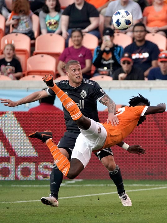 Houston Dynamo's Alberth Elis, right, dives for the ball in front of Vancouver Whitecaps's Marcel de Jong during the first half of an MLS soccer game Saturday, March 10, 2018, in Houston. (AP Photo/David J. Phillip)