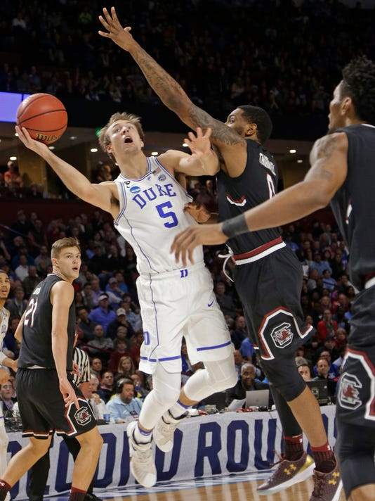 Duke's Luke Kennard (5) is fouled as he drives against South Carolina's Sindarius Thornwell (0) during the second half in a second-round game of the NCAA men's college basketball tournament in Greenville, S.C., Sunday, March 19, 2017. (AP Photo/Chuck Burton)