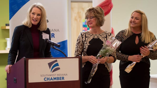 2016 Athena Award recipient and Southern Region CEO of Old National Bank Sara Miller, left, announces the 2018 Athena Award finalists while President at AlphaGraphics Lisa Slade, center, and owner and founder of Lamasco's Bar & Grill and The Dapper Pig Amy Word Smith, stand after being announced as finalists at the Southwest Indiana Chamber in Evansville, Ind., on Friday, Dec. 8, 2017. Word Smith and Slade are two of the twelve finalists.