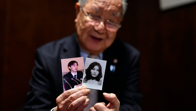 Shigeo Iizuka, 79, head of a group of families of Japanese abducted by North Korea, shows pictures of his abducted sister Yaeko Taguchi (right) and her son Koiichi Iizuka during an interview in Tokyo, Japan, Dec. 3, 2017.