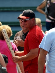 Manager David Balo holds a bat signed by the team as the Junior Pioneers players and coaches returned home to meet fans after the team won its first AAABA World Series title in 2016. Balo is among 12 people being inducted into the Old Timers Hall of Fame.