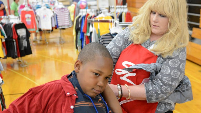 Green Bay Press-Gazette reporter Patti Zarling volunteers to help Joseph Daniels pick out clothing and school supplies during the Service League's 22nd Annual Back to School Store, at Green Bay East High School, Wednesday, August 6, 2014. H. Marc Larson/Press-Gazette Media
