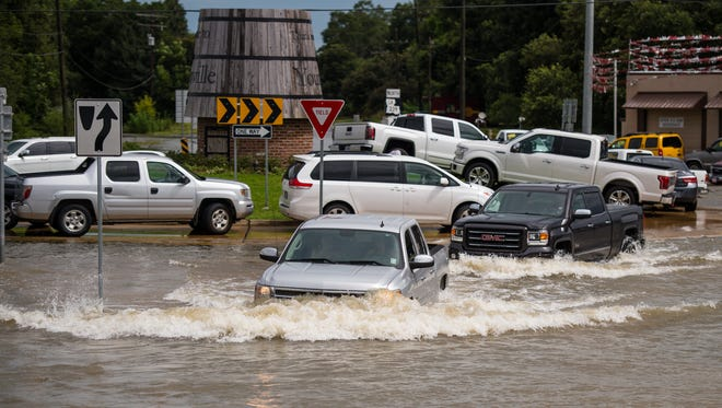 "Trucks attempt to drive through a flooded intersection in Youngsville, La., Sunday, Aug 14, 2016. Louisiana Gov. John Bel Edwards said Sunday that at least 7,000 people had been rescued so far. He declared a state of emergency Saturday, calling the floods ""unprecedented"" and ""historic."""
