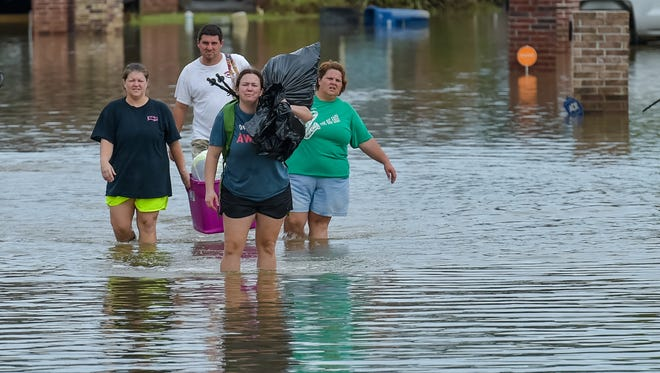 People wade in water near flood damaged homes in Highland Ridge Subdivision in Youngsville, La., Sunday, Aug. 14, 2016. Torrential rains swamped parts of southern Louisiana, causing widespread flooding.