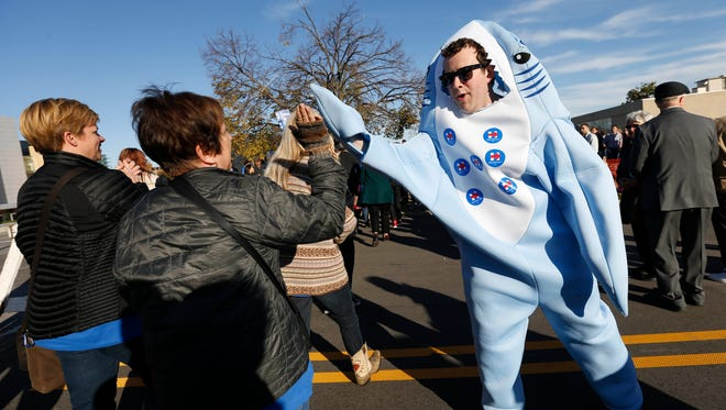 Campaign worker Dan Bram of St. Louis greets supporters dressed as Left Shark, one of the back-up dancers during Katy Perry's Superbowl performance, Saturday, Oct. 24, 2015 during a rally for Democratic presidential candidate Hillary Clinton before the Iowa Democratic Party Jefferson-Jackson Dinner in downtown Des Moines.