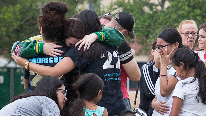 Santa Fe High School senior Amy Roden is embraced by a group of people next to a makeshift memorial in front of the school in Santa Fe, Texas on May 20, 2018.