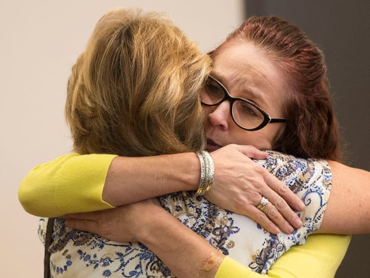 Carrie Giesler, right, hugs her friend and former co-worker,