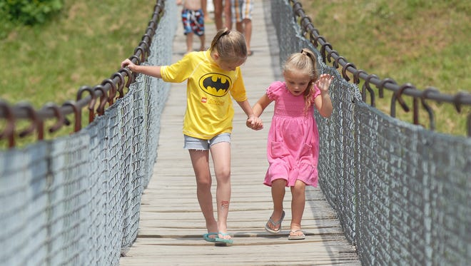 Cousins Lana Cooper and Jaylynn Maduri hold hands as they cross the swinging bridge in Croswell.