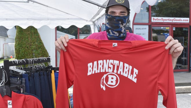 """Riley Ashe, a Barnstable High School alumnus and employee at Butler Sporting Goods, holds up one of the school's Red Raider logo shirts at the Hyannis store. The day after the School Committee voted to retire the mascot, the store received several calls from people hoping to buy the gear. The """"B"""" with feathers replaced an earlier logo featuring the profile of a Native American."""