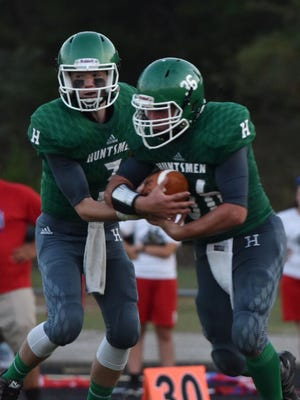 Huntington's Elijah McCloskey hands the ball off to Jesse Lewis during Week 3's 57-13 win over Northwest.