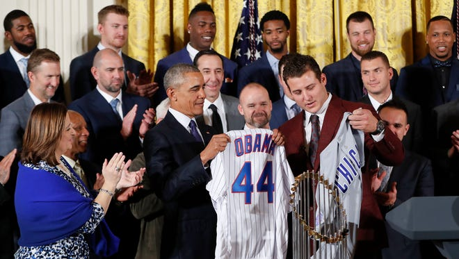 President Obama holds up a personalized Cubs jersey presented by the Cubs' No. 44, Anthony Rizzo.