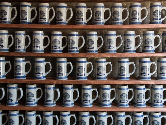 A wall filled with Founders Club mugs hangs inside