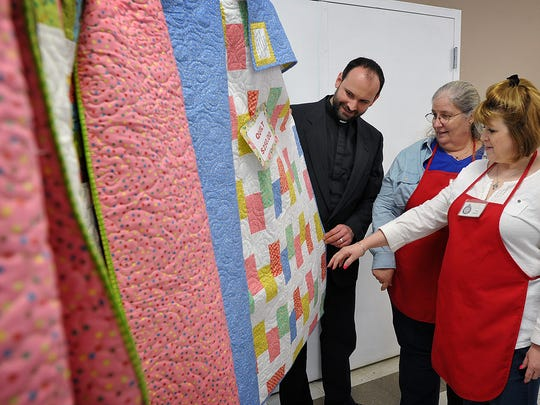 In this file photo, Father Brian Chase, Carol Skelton and Tracy Johnson, right, look over one of the handmade quilts the ladies sewed for the 2017 Annual Election Day Soup Lunch and Bazaar at The Church of the Good Shepherd. The 91st annual event will be held Nov. 5.