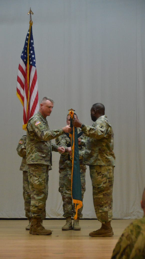 Maj. Gen. Terry McKenrick and Command Sgt. Maj. Wil Engram unveil the new Joint Modernization Command colors during the re-designation ceremony in February.