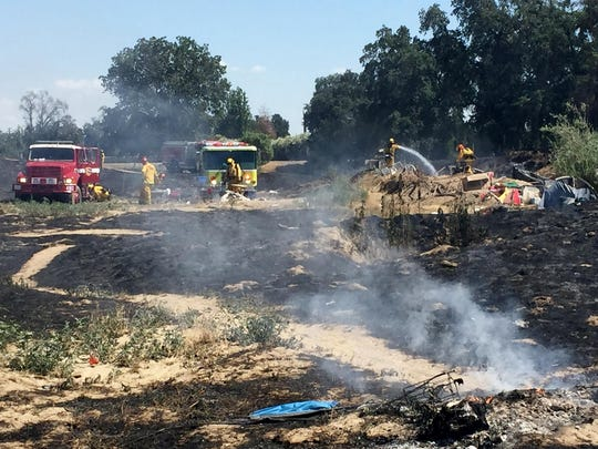Fire fighters put out hot spots Saturday afternoon after a fire burned through part of a homeless campsite on the north bank of the St. Johns River, just north of Visalia.
