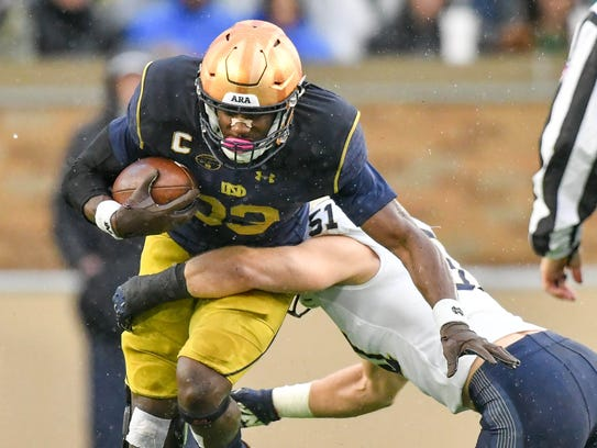 Fighting Irish running back Josh Adams (33) is tackled by Navy Midshipmen linebacker Winn Howard (51) in the first quarter at Notre Dame Stadium.