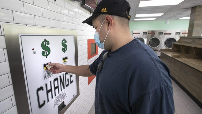 Adrian Aguilar gets change in quarters from a $5 bill at SpinCycle Laundry Lounge in Los Angeles, before feeding them into the washing machine and dryer to do his laundry. There is a nationwide coin shortage and laundromats have been particularly affected since customers might not always walk in with enough quarters to do their laundry.