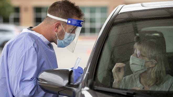 Registered nurse Keith M. prepares to take a sample from Irene Schmid at a drive-through COVID-19 test site at Austin Emergency Center on South Lamar Boulevard on July 8, 2020.