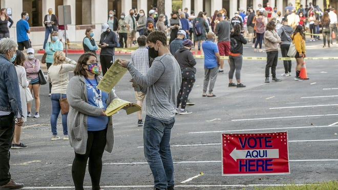 People wait in a long line to vote at an early voting location at the Renaissance Austin Hotel on October 13.