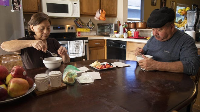 Maria and Nelson Toala eat breakfast in their home, where they also care for two of their granddaughters, who are 8 and 10. The Toalas moved from Ecuador to the United States in 2006. Nelson Toala had been the provider for his family and was working as a cook at the Driskill Hotel until he was furloughed because of the pandemic and then had a stroke.