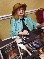 Actress Piper Laurie smiles as she meets fans and takes
