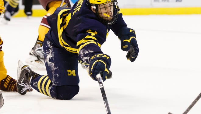 Michigan's Tyler Motte (14) dives for the puck in the second period against Minnesota during an NCAA college hockey game in the Big Ten Conference tournament Saturday, March 21, 2015, in Detroit.