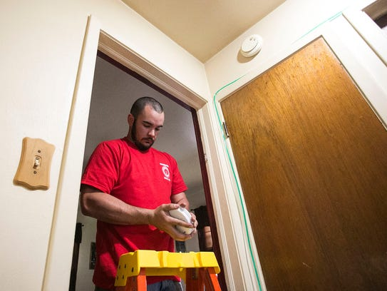 Electrician Jared Grim, of Springettsbury Twp., installs