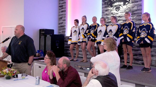 Pirate girls' hockey coach Tim Moe, with several of his players standing on stage, accepts a $2,500 grant for the girls' program at the Crookston Eagles Thursday evening.