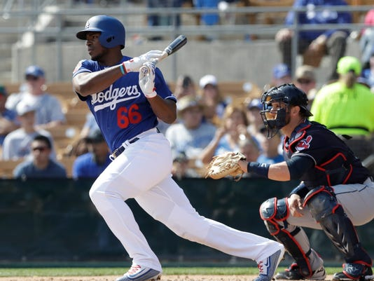 FILE- In this March 1, 2018, file photo, Los Angeles Dodgers' Yasiel Puig bats during the second inning of a spring training baseball game against the Cleveland Indians in Glendale, Ariz. Puig is coming off a career-high 28 home runs and his defensive excellence in right field remains intact, having salvaged his career in Los Angeles after being demoted to Triple-A in 2016 and nearly traded.  (AP Photo/Carlos Osorio, FIle)