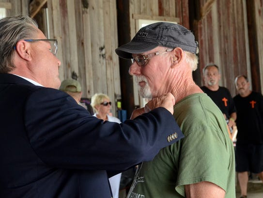 Nason Herron, of Alpena, receives his recognition pin