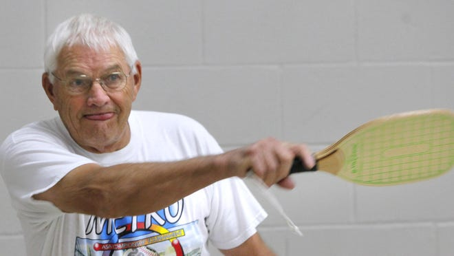 Bill Ries returns a shot in a pickleball match at the Dunham Recreation Center in East Price Hill. Pickleball is a paddle sport that combines elements of badminton, tennis and table tennis. It is played with a Wiffle ball at a slow speed.
