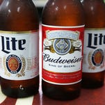 In this photo illustration, bottles of Budweiser and Miller Lite beer are seen on Sept. 16, 2015, in Miami, Fla.